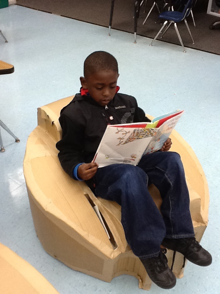 elementary student reading in chair