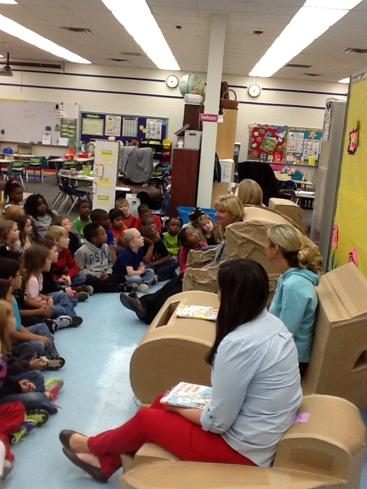 elementary students and teachers reading on chairs