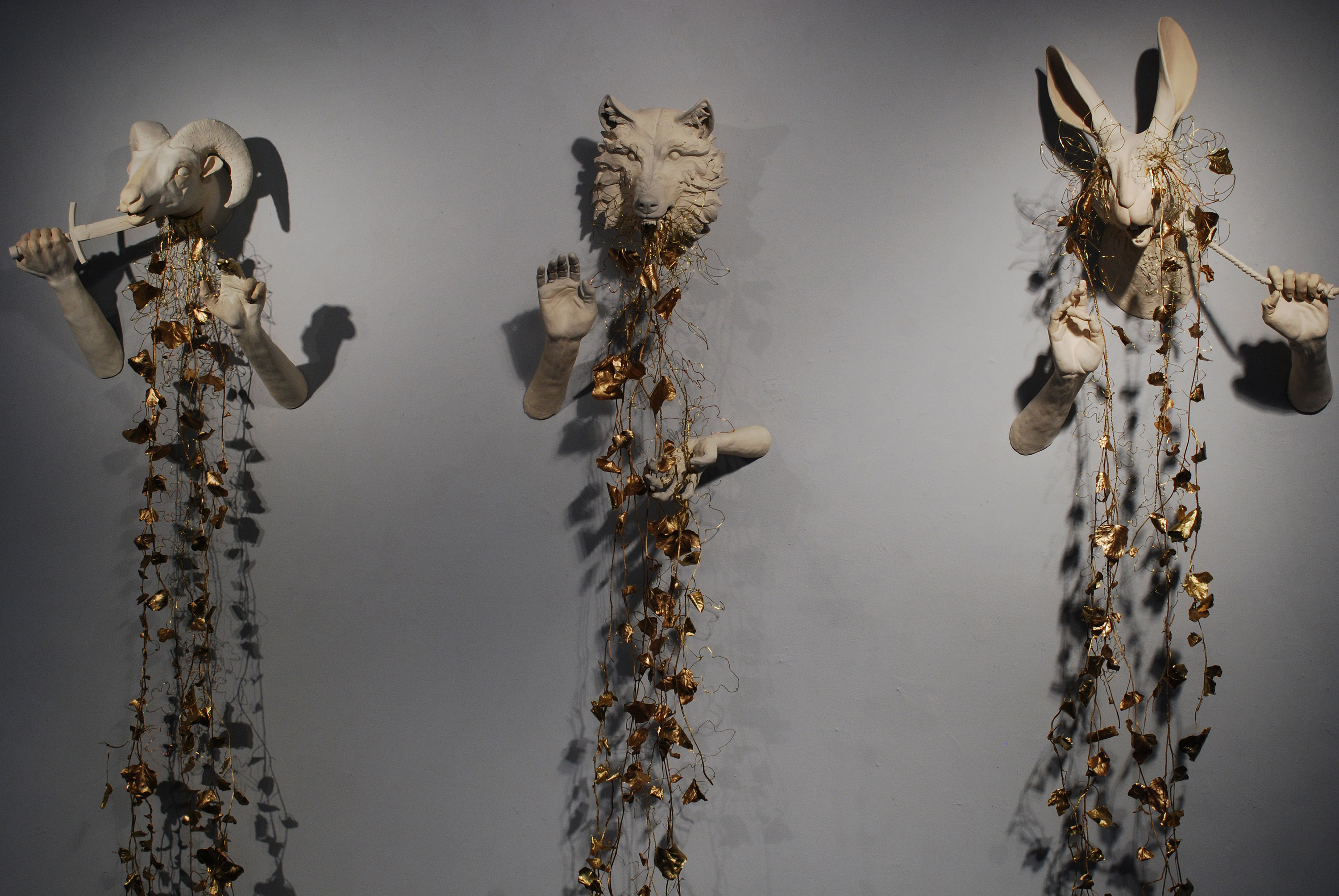 Three sculptures hanging on a wall. A goat, a wolf, and a rabbit.
