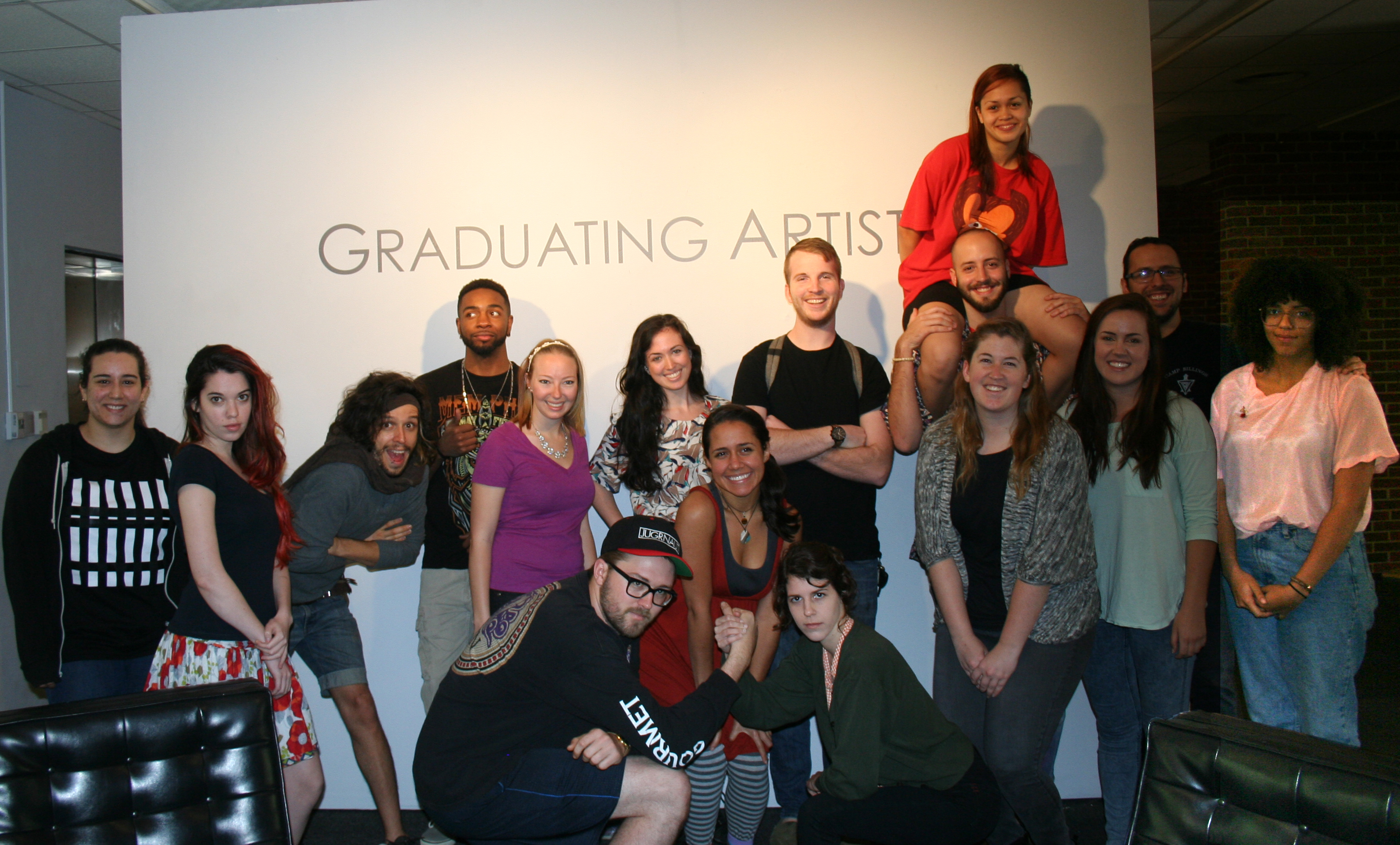 "group of students standing in front of a wall that says ""graduating artists"""