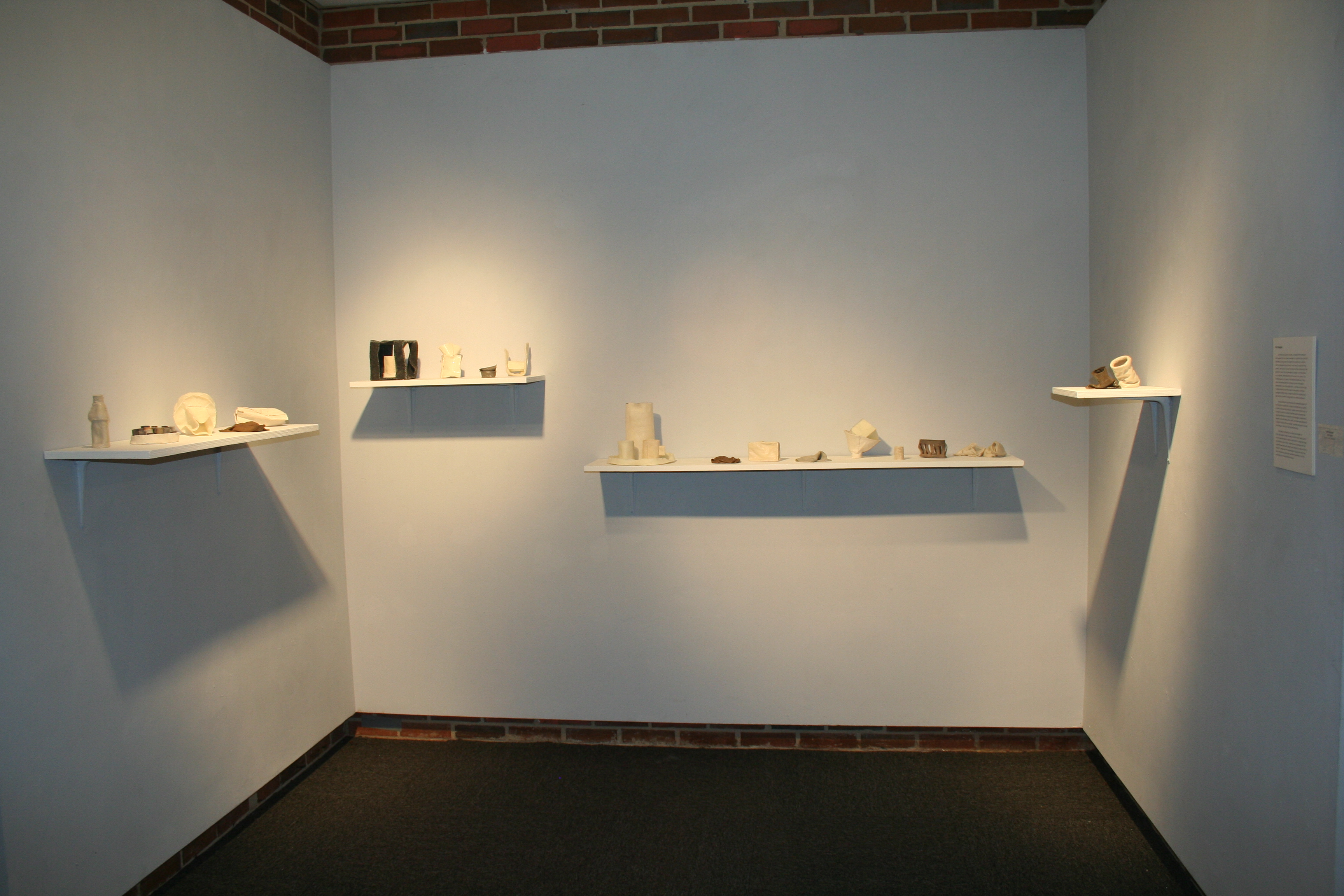 Display of hand made shapes on a shelf in a gallery space