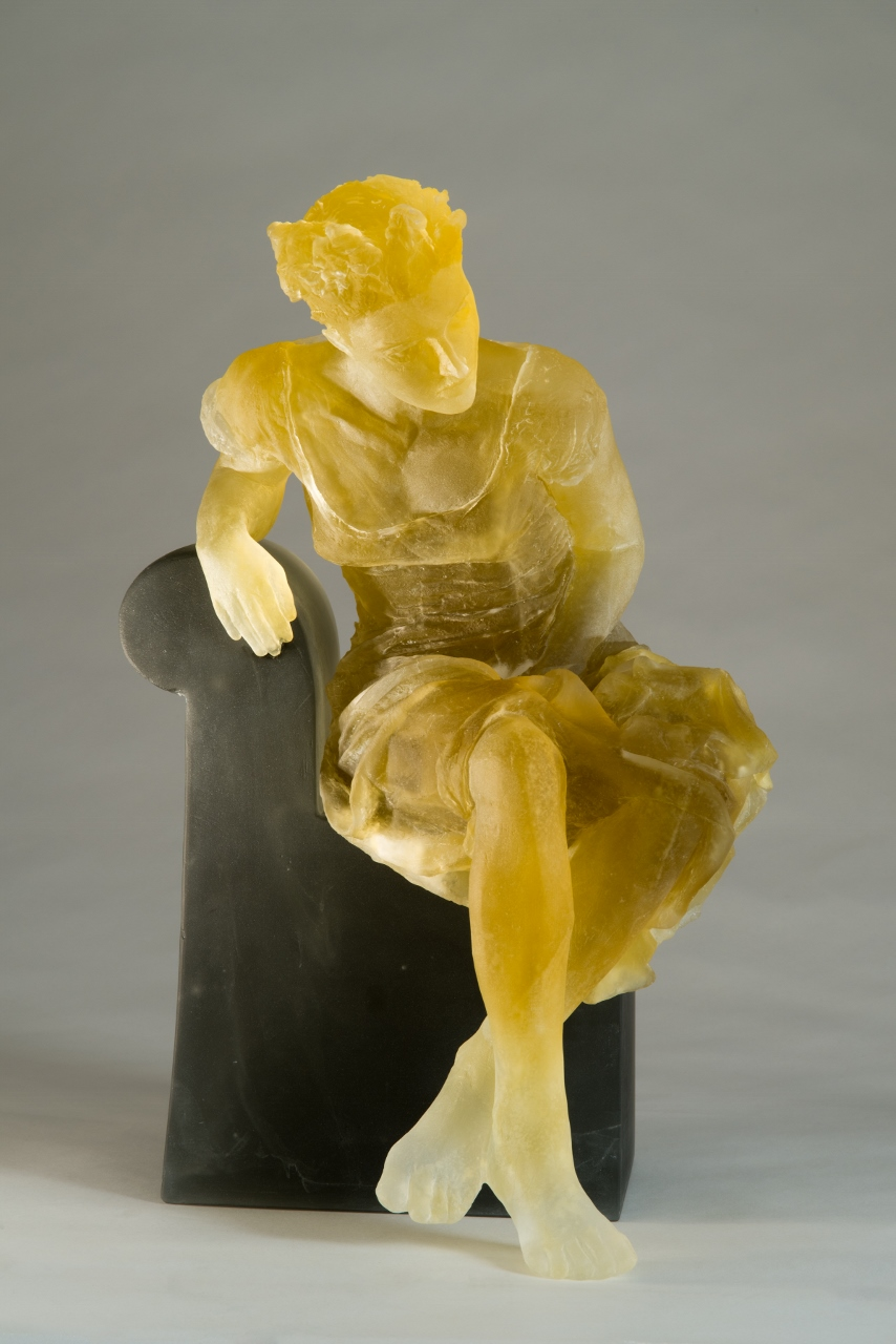 yellow sculpture of a seated figure