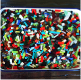 Glass pieces used to make fused glass necklaces in a workshop for young girls.