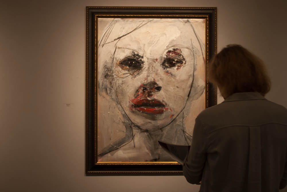 woman in front of painting