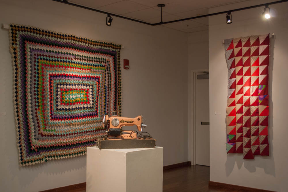 Angled shot of sewing machine in-between two quilts