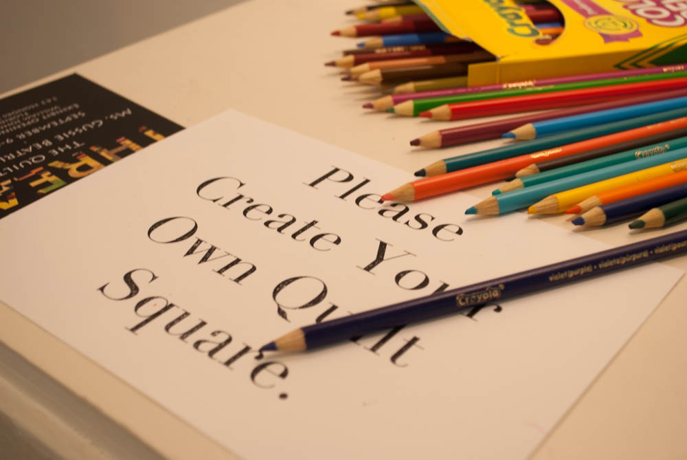 "Color pencils on sign that says ""Please Create Your Own Quilt Square."""