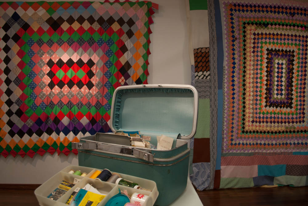 Sewing box and supplies in front of two quilts