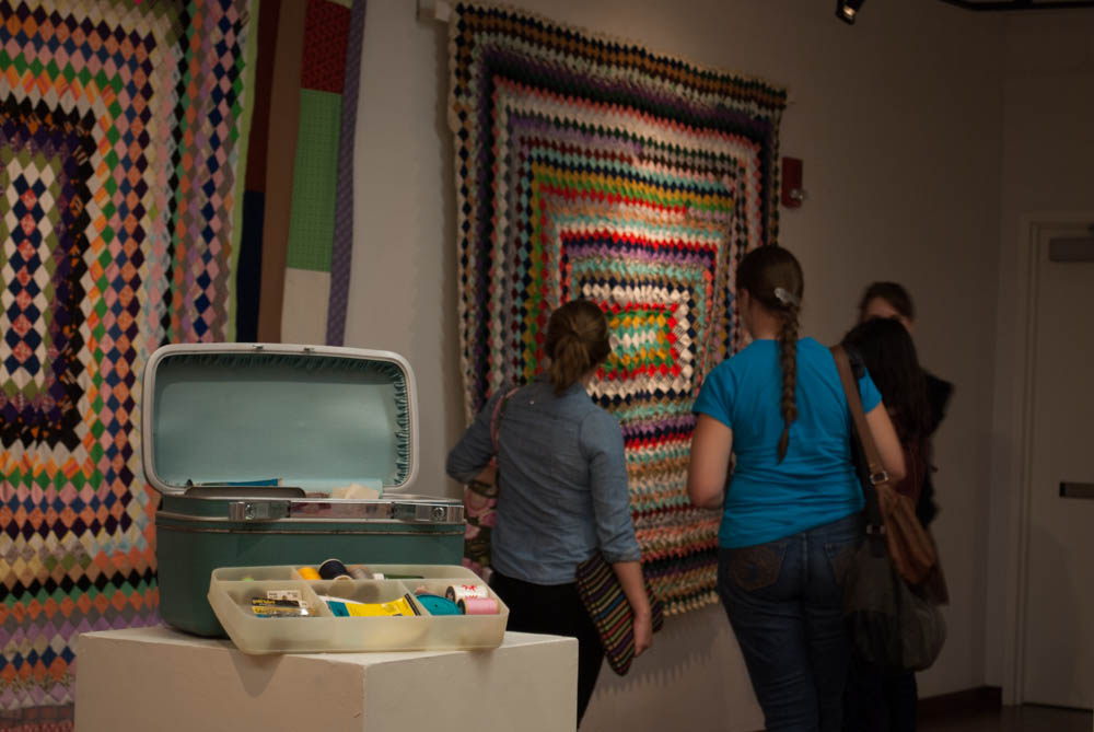 Guests looking at a quilt behind sewing supplies