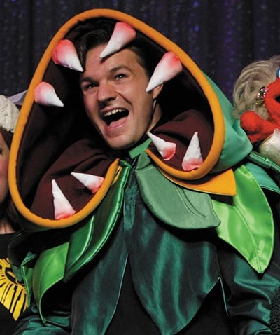Man in green costume with teeth in the hood