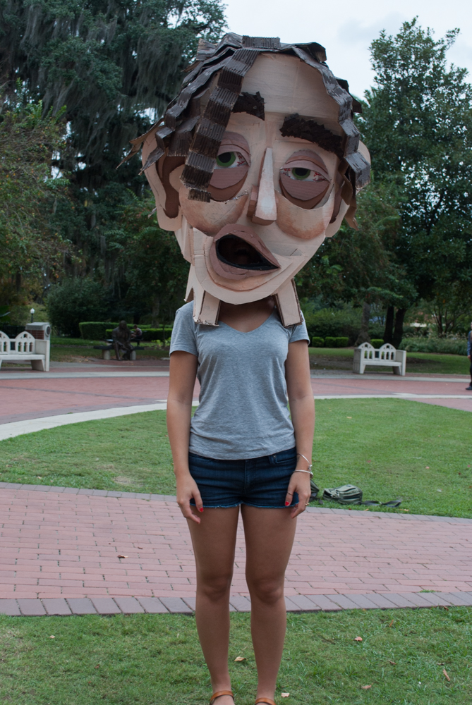 Straight on photo of female student with cardboard head