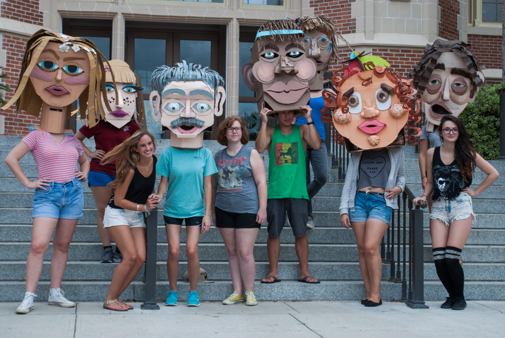 Students pose with cardboard heads in front of Westcott