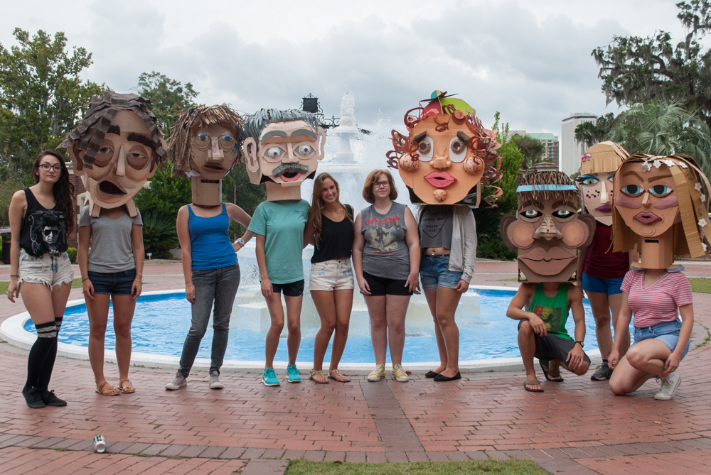 Students pose with cardboard heads in front of fountain