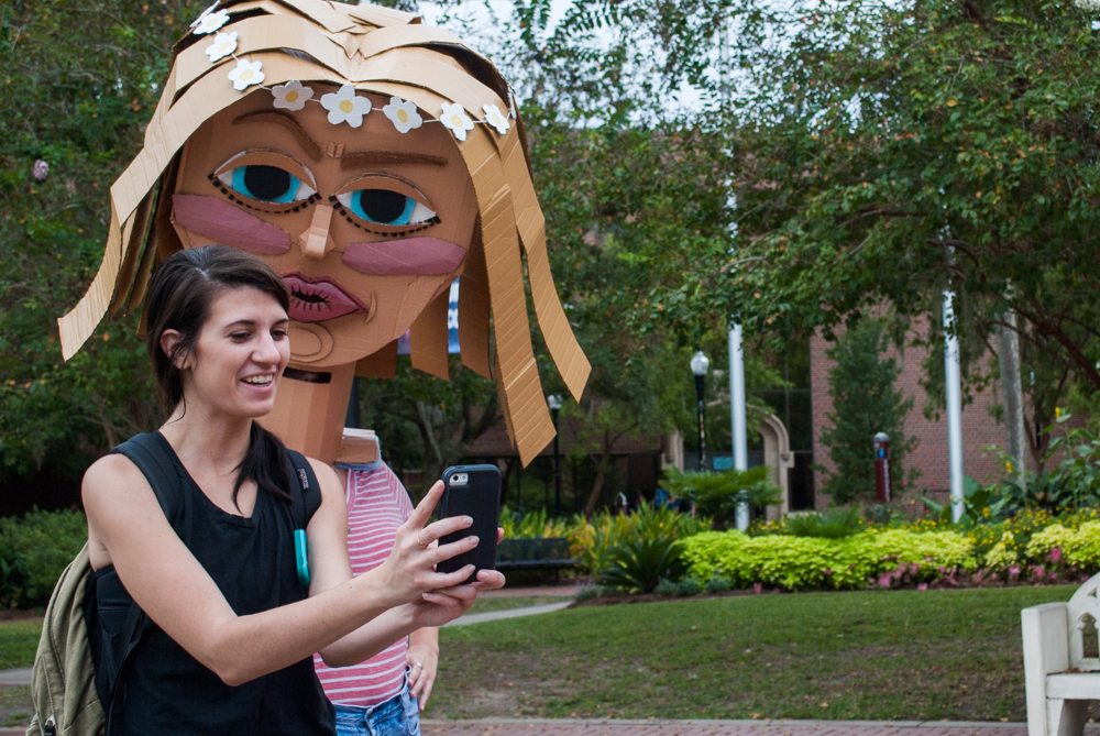 A female student and cardboard head share a photo that was taken