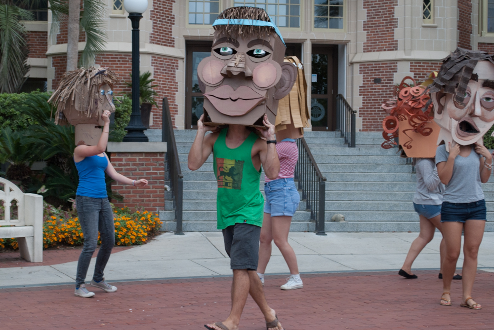 Male student with cardboard head dancing