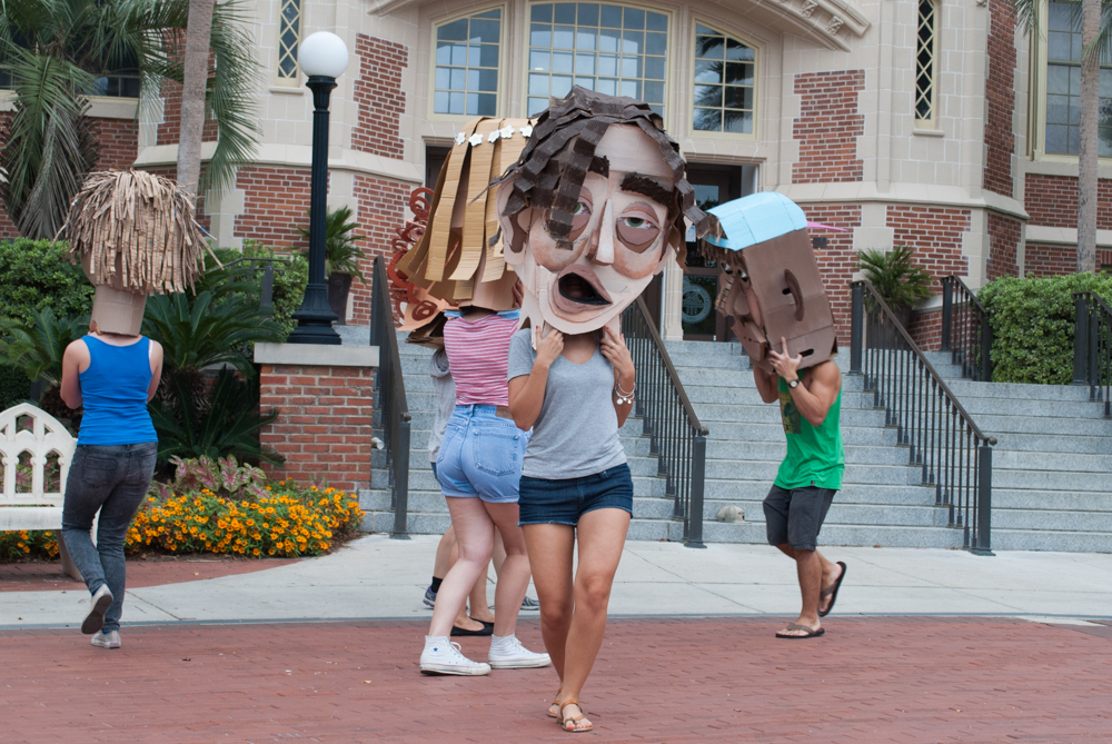 Female student with cardboard head dancing