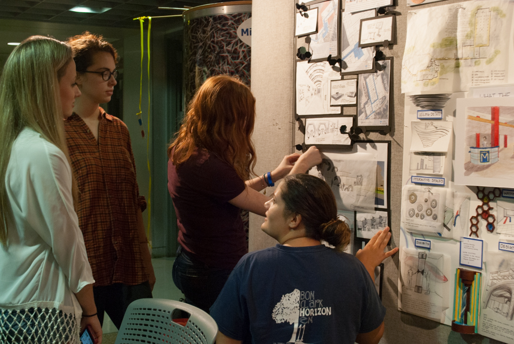 Three girls discussing and hanging their project