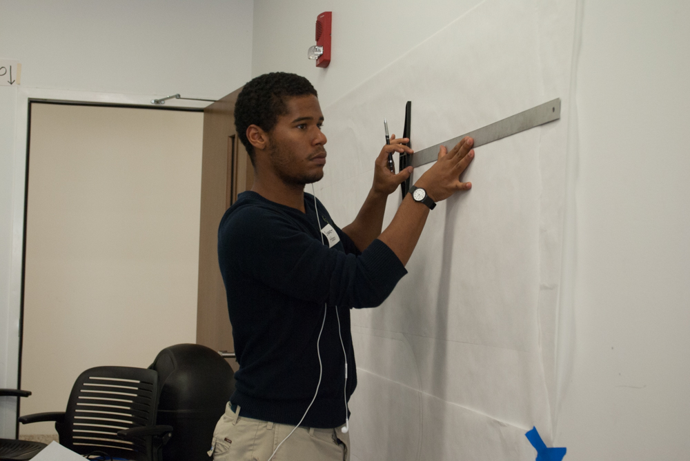 Side shot of a student drawing and measuring