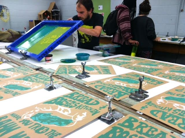 Tarek Patton printing the second run on his poster for Bread and Roses