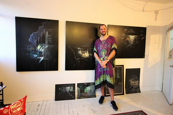 Miami artist Alex Zastera of Studio 84 stands beside his work which features night-time scenes of Miami structures that are in danger of disappearing due to development and gentrification.