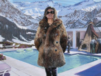 A woman with a fur coat, standing before a pool and mountains