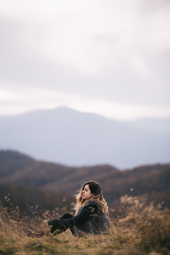 Young woman in grass, overlooking mountains.