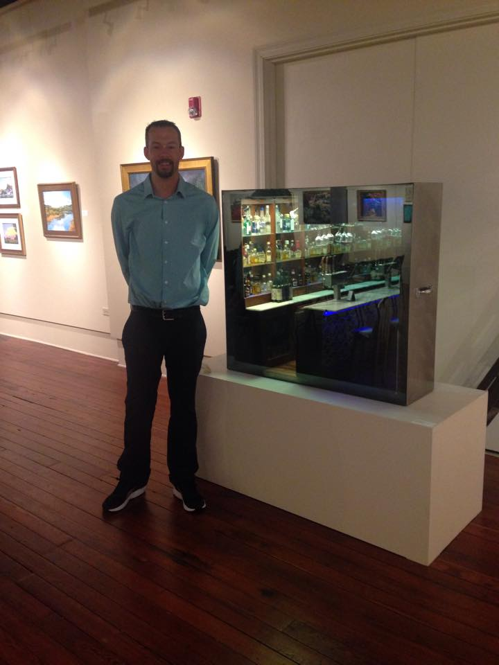 Phil Gleason stands in exhibition with his piece.