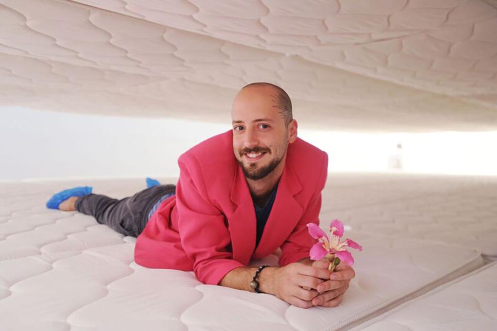 Alexander, holding a flower, poses between mattresses.