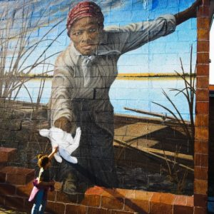 "A photo captured by Tracy Lynndee in Cambridge, Maryland of her 3-year-old granddaughter, ""Lovie"" Hope Duncan touching the hand of abolitionist Harriet Tubman has become a viral sensation on the internet. (Photo: Tracy Lynndee/Special to the Democrat)"